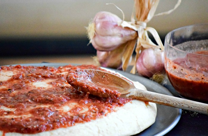 Homemade garlic pizza sauce tastes better, saves money and can be made ahead and frozen for a busy weeknight dinner solution.
